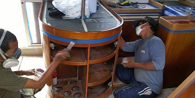 Baw and Pla brushing epoxy on high wear areas of the galley