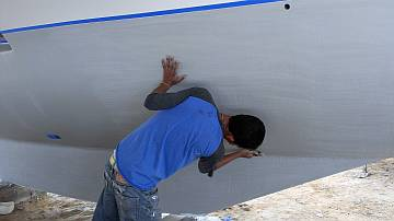 Baw roughing up the hulls so the antifouling sticks