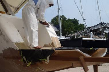 Boy grinding the gelcoat off stbd transom, above extension
