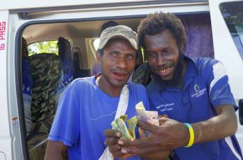Bus helper hams it up with fistful of Kina, PNG
