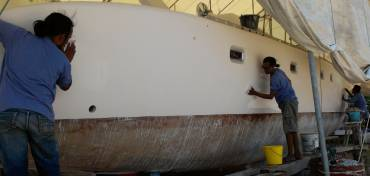 Chai, Lek & Yoong wet-sanding the starboard topsides with 600
