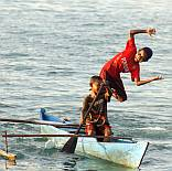 Papuan boys jump from canoe.