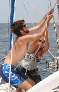 Chris & Amanda haul up the mainsail together.