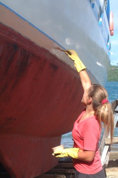 Amanda applies epoxy primer to her newly raised waterline