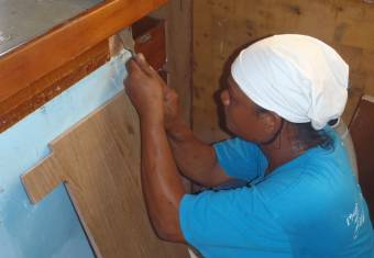 Houa fitting a piece of teak plywood into the galley