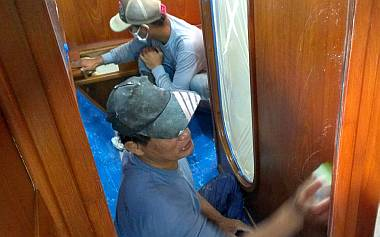 Heru and Pla sanding yesterday's spray inside the port aft cabin