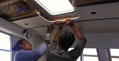 Houa and Baw test-installing a headliner over the galley