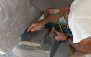 Jon chiseling off old antifouling paint from around the supports