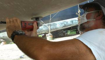 Grinding off old gelcoat from the bottom of the starboard hull