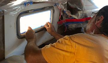 Jon mounting the glooped up starboard salon port-light
