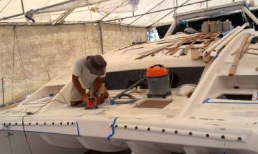 Jon sanding where the nonskid will go, on Ocelot's foredeck
