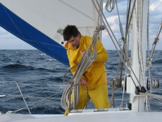 Jon reefs the mainsail, mid-Channel