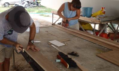 Amanda cutting frames with a jig-saw while Jon trims & smoothes them