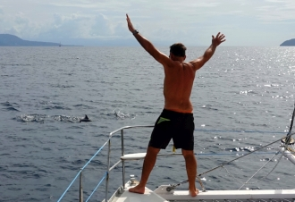 Jon waving to dolphins swimming off our bows