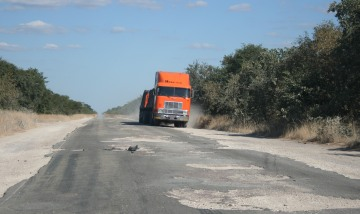 Potholes in Botswana force even big trucks off road.