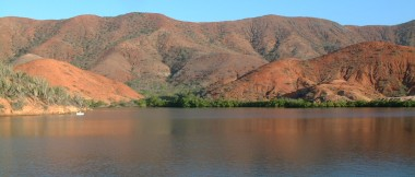 The beautiful green-fringed red hills of Laguna Grande