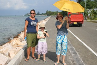 Walking the one paved street on Feydoo beside the lagoon with Abby and Eliza