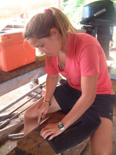 Amanda cuts new rubber flaps (from truck tire flaps) to seal the saildrives.