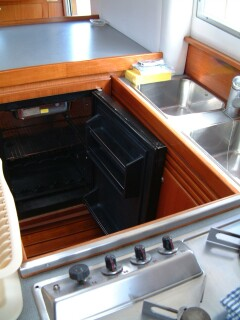Old galley fridge, with door open, before the conversion.  Note holding plate at top.