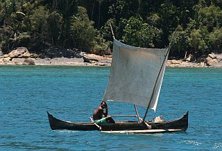 Tiny outrigger pirogue sailing happily