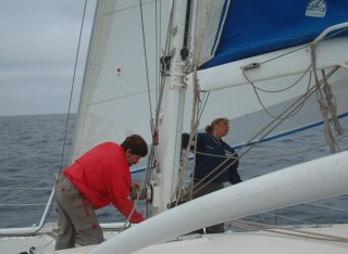 Shaking out a reef - note the unusual windbreakers & long pants