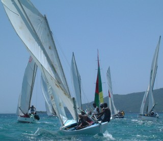 A group of sloops racing hard on the wind