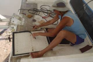 Sue removes the old flat gasket from a hatch cover