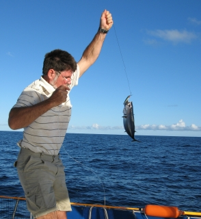 Jon pulls in a tuna. No help from Amanda with the fish, now!