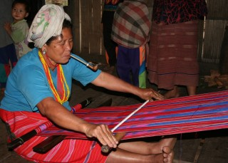 A Karen woman weaves in the hilltribe village