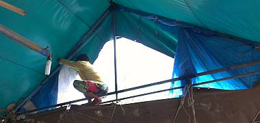 Yando perched at the top of Houa's workshop, replacing a tarp