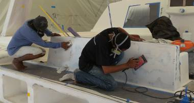 Yoong & Baw sanding the epoxy sealer on the aft cockpit seat